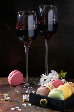 Two glasses of port wine with variety of colorful french sweet dessert macaron macaroons with different fillings served with spring flowers over dark texture background. Stock Photo - 77410575