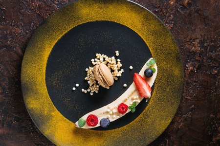 Food plating dessert organic banana with fresh berries, mint, puffed rice and macaroon biscuit served with turmeric powder on black plate over brown texture background. Flat lay, space Stock Photo