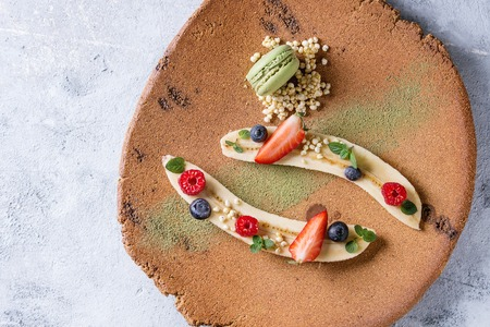 Food plating dessert organic banana with fresh berries, mint, puffed rice and macaroon biscuit served with green tea matcha powder on terracotta plate over gray texture background. Flat lay, space Stock Photo