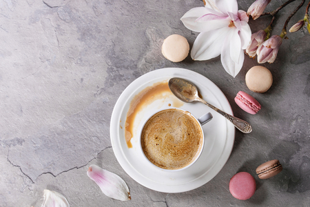 White cup of black coffee, served on white saucer with macaroons biscuits, spoon and magnolia flower blossom branch over gray texture background. Flat lay, space Imagens