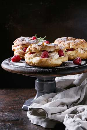 Homemade choux pastry cake Paris Brest with raspberries, almond and rosemary, served on black wooden serving board on cake stand over dark texture background. French dessert