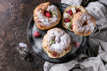 Homemade choux pastry cake Paris Brest with raspberries, almond, sugar powder and rosemary, served on black wooden serving board over dark texture background with textile. French dessert. Top view Banco de Imagens