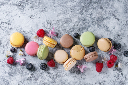 Variety of colorful french sweet dessert macaron macaroons with different fillings served with spring flowers and berries over gray texture background. Top view with space Stock Photo