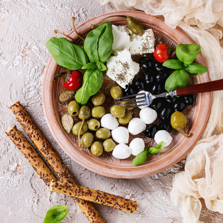 Mediterranean appetizer antipasti plate with green black olives, feta cheese, mozzarella, capers, pepper, basil with grissini bread sticks over beige concrete texture background. Top view. Square image