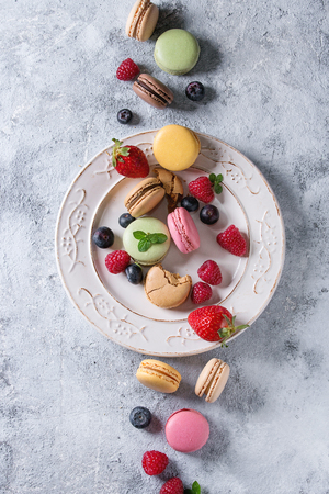 Variety of colorful french sweet dessert macaron macaroons with different fillings served on white vintage plate with spring flowers and berries over gray texture background. Top view with space