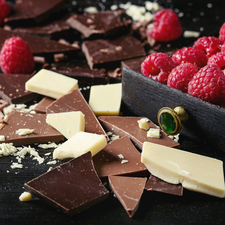Variety of dark, milk and white chopping chocolate with fresh raspberries in black wood box over black burnt wooden background. Close up. Chocolate dessert concept. Square image Imagens - 78359377