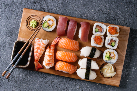 木製サービング船上醤油と黒の石のテクスチャの背景の上の箸セット握りと寿司ロールを寿司。領域での平面図です。日本のメニュー