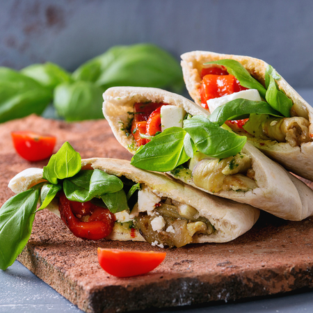 Pita bread sandwiches with grilled vegetables paprika, eggplant, tomato, basil and feta cheese served on terracotta board over gray stone background. Close up. Healthy fast food. Square image Stock Photo