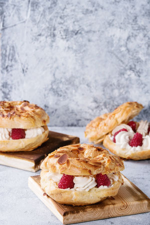 Homemade choux pastry cake Paris Brest with raspberries, almond and rosemary, served on wooden serving board over gray blue texture background. French dessert Banco de Imagens