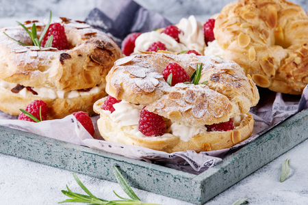 Homemade choux pastry cake Paris Brest with raspberries, almond, sugar powder and rosemary, served on wooden serving tray over gray blue texture background. French dessert. Close up