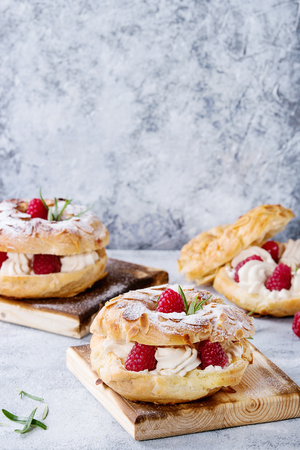 Homemade choux pastry cake Paris Brest with raspberries, almond, sugar powder and rosemary, served on wooden serving board over gray blue texture background. French dessert Banco de Imagens