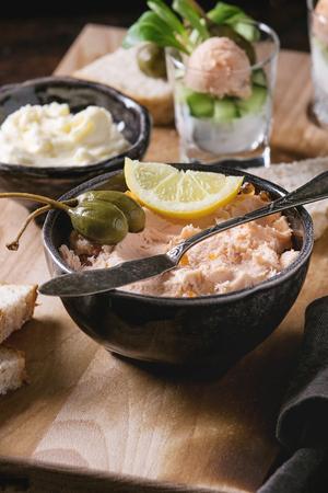 Tazón de fuente de salmón negro con caviar rojo servido con mantequilla, pan rebanado, alcaparras, cuchillo de la vendimia, verrines y hierbas en tablero de madera de la porción, lino textil sobre fondo de la textura marrón. De cerca