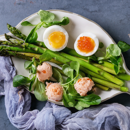 Cooked green asparagus with half boiled egg, salad, red caviar and salmon pate served on white fish shape plate with gauze textile over gray blue texture metal background. Top view. Square image