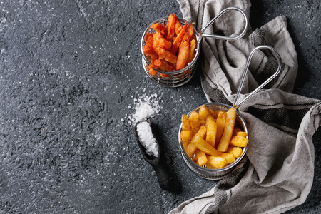 Variety of french fries traditional potatoes, sweet potato, carrot served with white salt, thyme in frying basket over dark texture background. Top view with space. Homemade fast food