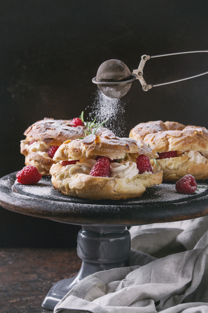 Homemade choux pastry cake Paris Brest with raspberries, almond and rosemary, served on black wooden serving board on cake stand over dark texture background. Sprinkling sugar powder. French dessert Banco de Imagens