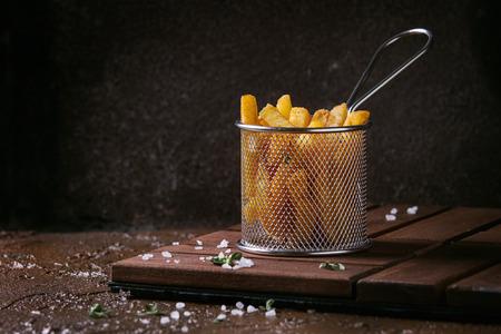 伝統的なフレンチ フライ ポテトは、茶色のテクスチャの背景の上で木の板に塩、タイム バスケットをフライパンで提供しています。手作りのファ