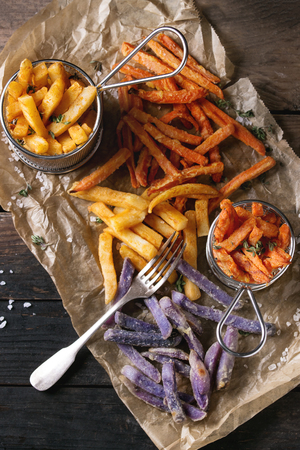 Variety of french fries traditional potatoes, purple potato, carrot served with salt, thyme and fork on baking paper over old wooden background. Top view with space. Homemade fast food Stock Photo
