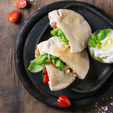 Pita bread sandwiches with grilled vegetables paprika, eggplant, tomato, basil and feta cheese served on black chopping board over dark wooden background. Healthy fast food. Top view. Square image Stock Photo
