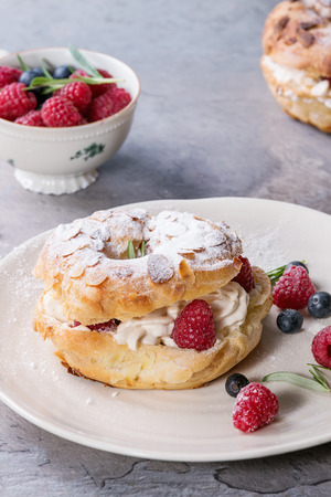 Homemade choux pastry cake Paris Brest with raspberries, almond, sugar powder, rosemary on white plate with berries over gray texture background. French dessert. Banco de Imagens