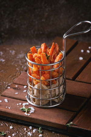 Seet potato or carrot french fries served in frying basket with salt, thyme on wooden board over brown texture background. Homemade fast food Stock Photo