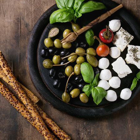 caper: Mediterranean appetizer antipasti board with green black olives, feta cheese, mozzarella, capers, pepper, basil with grissini bread sticks over old wooden background. Top view. Square image