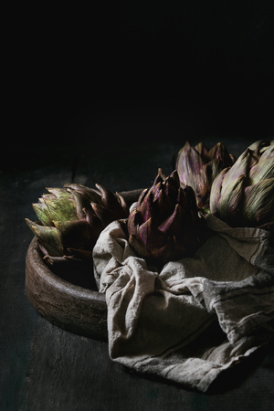 Uncooked whole organic wet purple artichokes in terracotta tray with textile over dark wooden background. Rustic style. Reklamní fotografie