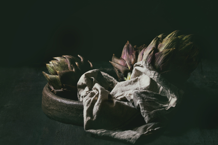 Uncooked whole organic wet purple artichokes in terracotta tray with textile over dark wooden background. Rustic style. Toned image