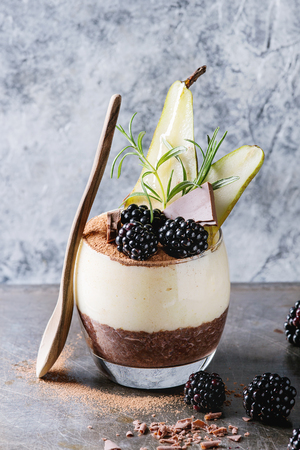 Dessert breakfast layered chia seeds, chocolate pudding, rice porridge in glass decorated by fresh blackberries, sliced pear, cocoa powder. Stand with spoon over gray texture background.