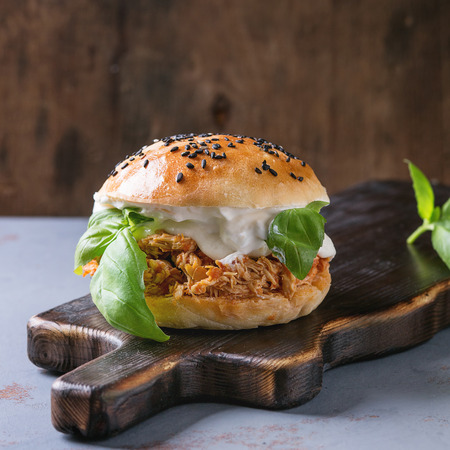 Homemade mini burger with pulled chicken, basil, mozzarella cheese and yogurt sauce on wooden serving board over gray texture background. Healthy fast food concept. Square image