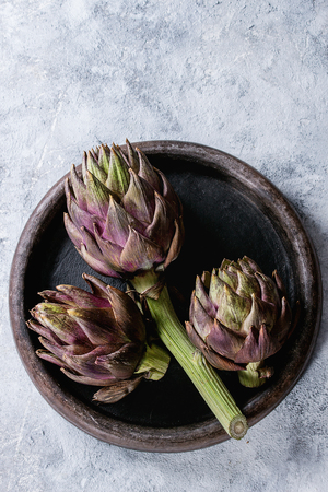 Uncooked whole organic wet purple artichokes in terracotta tray over gray texture background. Top view with space Reklamní fotografie