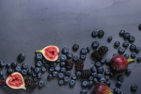 様々 な新鮮な果実ブルーベリー、デューベリー、暗い金属を背景にイチジク。領域での平面図です。