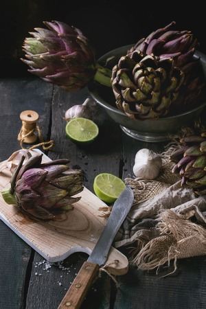 Uncooked whole organic wet purple artichokes in vintage bowl and on wood chopping board with lime, garlic, thread, textile sackcloth over dark wooden background. Rustic style.