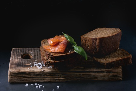 Stack of sliced homemade rye bread with smoked salmon, sea salt and fresh basil on wooden chopping board over dark black background.