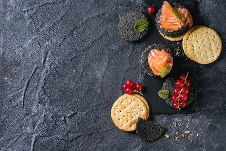 黒全粒炭と伝統のスタック黒石背景にスモーク サーモン クラッカー、クリーム チーズ、グリーン サラダ、スレートの赤スグリの果実ボードします 写真素材