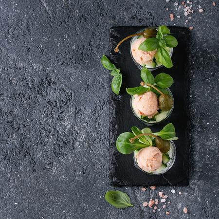 Verrines apéritif au pâté de saumon, caviar rouge, concombre, fromage à la crème, herbes, câpres dans des verres servis avec du sel rose, basilic sur ardoise noire sur fond de texture grise. Vue de dessus. Image carrée