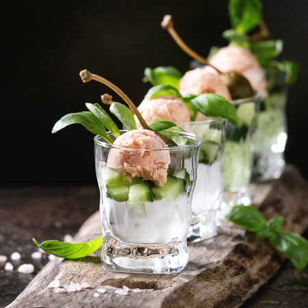 Verrines appetizer with salmon pate, red caviar, cucumber, cream cheese, herbs, capers in glasses served with pink salt and basil on wooden serving board over brown texture background. Square image