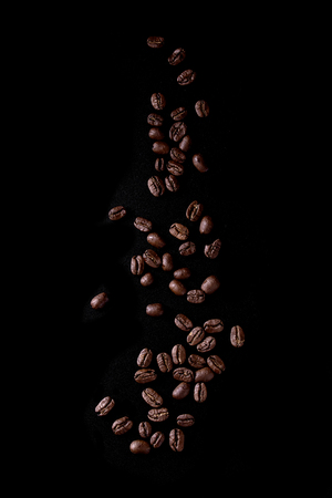 Roasted coffee beans over black background. Isolated