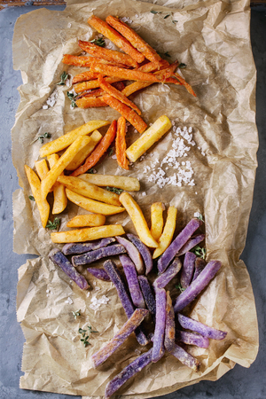 Variety of french fries traditional potatoes, purple potato, carrot served with salt, thyme on baking paper over gray metal background. Top view with space. Homemade fast food