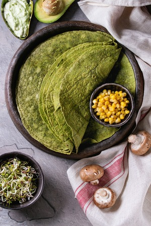 Green spinach matcha tortilla with vegan ingredients for filling. Sweet corn, avocado, green paprika, sprouts, mushrooms served in terracotta plate over gray texture background and textile. Flat lay