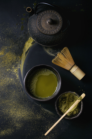 Green tea matcha powder and hot drink in black bowls standing with iron teapot, bamboo traditional tools spoon and whisk over dark metal background. Top view with space Reklamní fotografie