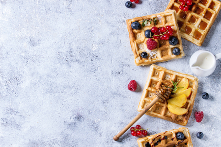 Homemade square belgian waffles with fresh ripe berries blueberry, raspberry, red currant, peach served with caramel, balsamic sauce, honey, jug of cream over gray background. Top view with space Reklamní fotografie