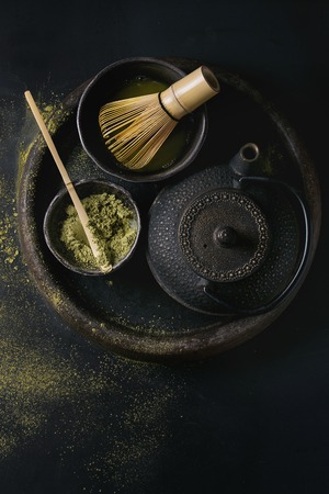 maccha: Green tea matcha powder and hot drink in black bowls standing with iron teapot, bamboo traditional tools spoon and whisk in terracotta tray over dark metal background. Top view with space