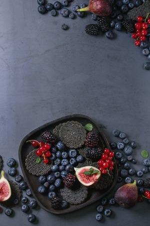 様々 な新鮮な果実ブルーベリー、デューベリー、レッドカラント、暗い金属を背景に木の板に黒い炭クラッカーとイチジク。領域での平面図です。