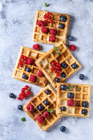 Homemade square belgian waffles with fresh ripe berries blueberry, raspberry, red currant over gray texture background. Top view with space Reklamní fotografie