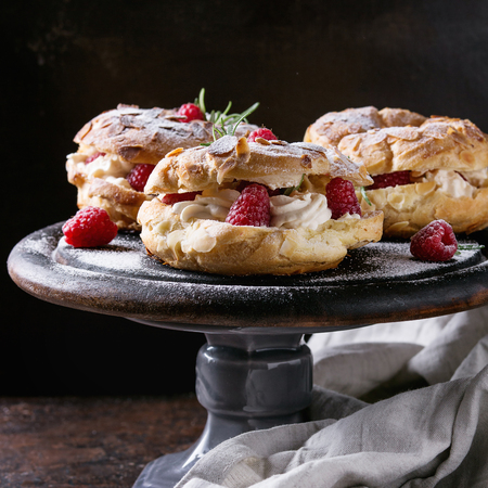 Homemade choux pastry cake Paris Brest with raspberries, almond and rosemary, served on black wooden serving board on cake stand over dark texture background. Banco de Imagens
