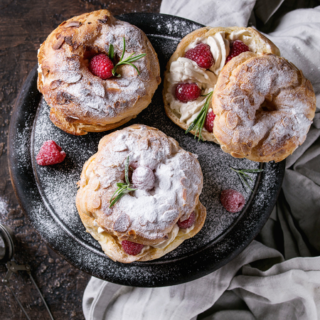 Homemade choux pastry cake Paris Brest with raspberries, almond, sugar powder and rosemary, served on black wooden serving board over dark texture background with textile. Top view. Square image Banco de Imagens