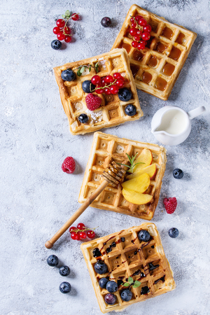 Homemade square belgian waffles with fresh ripe berries blueberry, raspberry, red currant, peach served with caramel, balsamic sauce, honey, whipped cream over gray background. Top view with space Zdjęcie Seryjne