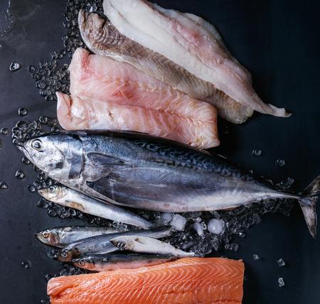 生の新鮮な魚の様々 な。全体のマグロ、ニシン、暗い湿式金属を背景に砕いた氷のサーモン、タラ、赤魚の切り身。領域での平面図です。魚市場概 写真素材