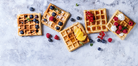 Homemade square belgian waffles with fresh ripe berries blueberry, raspberry, red currant, peach served with caramel, balsamic sauce, honey, whipped cream over gray background. Top view with space Stockfoto
