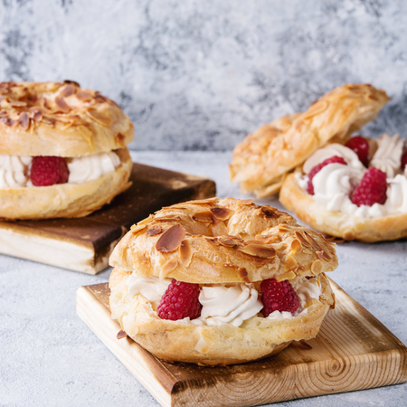 Homemade choux pastry cake Paris Brest with raspberries, almond and rosemary, served on wooden serving board over gray blue texture background. French dessert. Square image